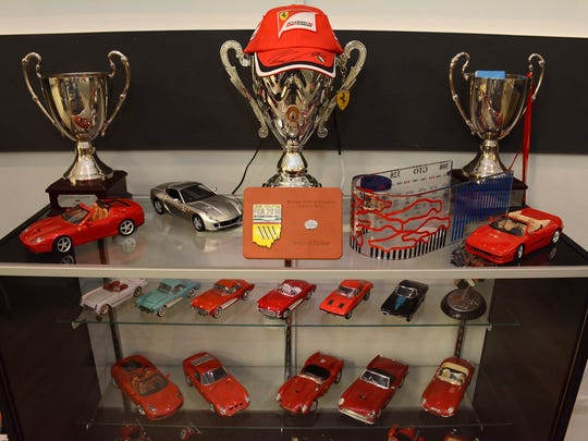Trophies and models of some of Young's collection.  Owning 16 collectible - and drivable - cars, plus six classic motorcycles, Marco Islander Bill Young built a house to hold them, with the entire ground floor laid out as a 16-car garage.