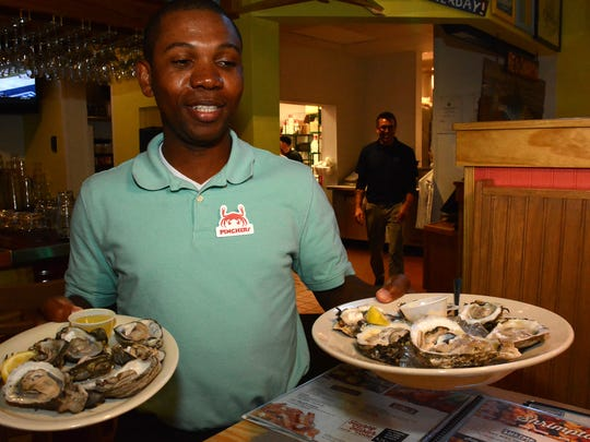 Server Brewton Jeffery serves oysters. Pinchers, the Southwest Florida chain of seafood restaurants, has opened its newest location next to the Marco Walk Plaza.
