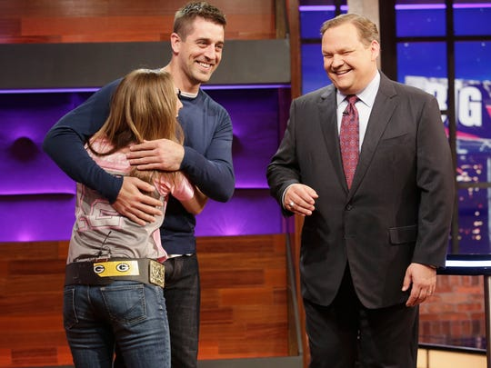 "Cassandra Hooyman, a nurse from Marshfield, gets a hug from Aaron Rodgers as host Andy Richter looks on during ABC game show ""Big Fan."""