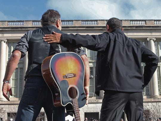 Bruce Springsteen  welcomes U.S. President Barack Obama to the stage during a rally on the last day of campaigning in the general election November 5, 2012 in Madison, Wisconsin.