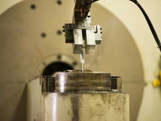 A robotic arm removes a section of wire from a computerized two-dimensional bending machine before carrying it to an automated welder at Marlin Steel in Baltimore, which has embraced automation to remain competitive with foreign manufacturers.