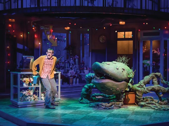 "Nerdy florist's assistant Seymour (Nick Cearley), with his murderous exotic plant Audrey II (voice by Chaz Rose, manipulation by Stephen Kriz Gardner) in the Playhouse in the Park's production of ""Little Shop of Horrors."""
