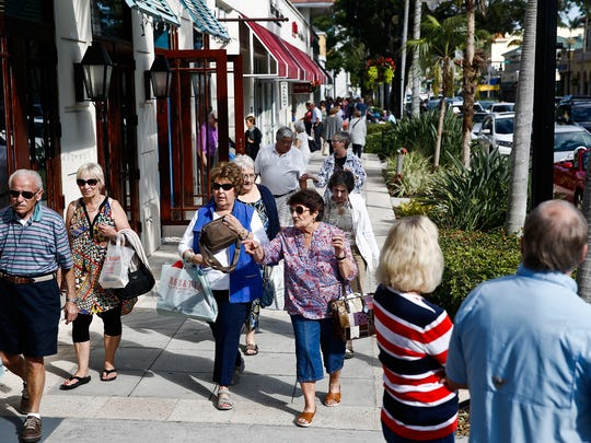 People stroll up and down Fifth Avenue South in Naples visiting shops and dining at restaurants on Monday, Jan. 25, 2016.