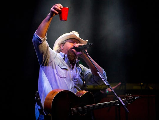 Toby Keith lifts up a cup during his performance at