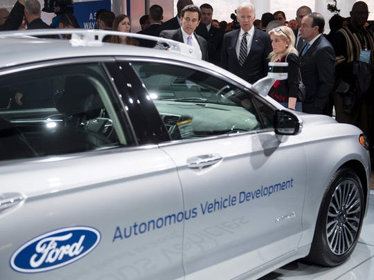 President and CEO of Ford Motor Company Mark Fields talks with Vice President Joe Biden and Congresswoman Debbie Dingell, D-Michigan next to the Ford Fusion autonomous vehicle while touring the 2017 North American International Auto Show in Detroit, January 10, 2017.