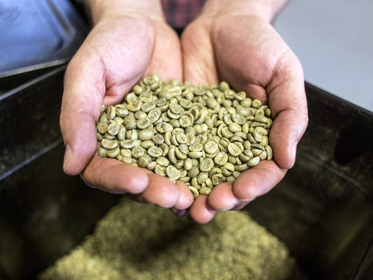 Bill Tanner, PennyCup Coffee Co. owner, holds up pre-roasted green coffee beans from a freshly shipped bag.
