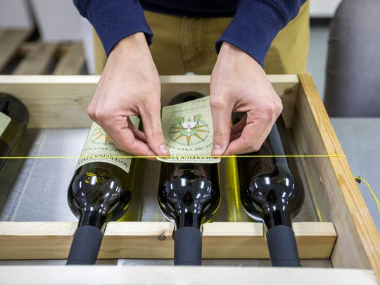 Kaelan Castetter labels bottles of his hemp-infused wine at the Sovereign Vines facility in Johnson City.