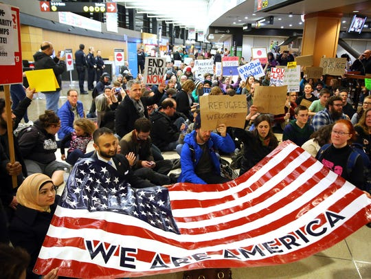 Demonstrators sit down in the concourse and hold a