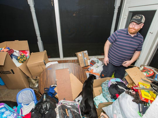 Mike Chandler stands among donations his family received
