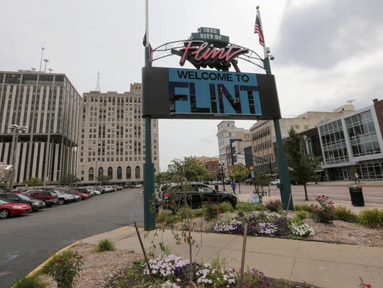 A video sign flashes a Welcome to Flint sign off of