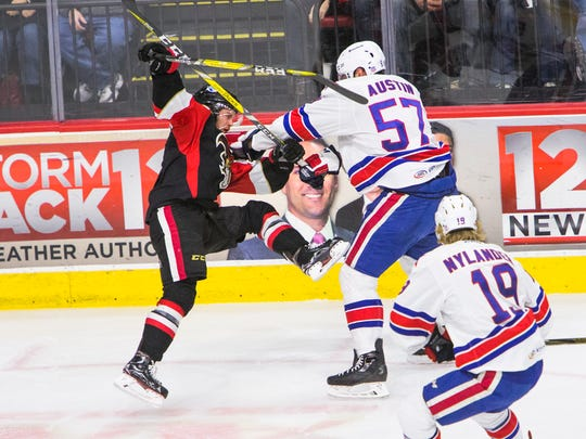 Binghamton Senators center Kyle Flanagan is knocked into the air by Rochester Americans defenseman Brady Austin during the first period in Binghamton on Saturday.