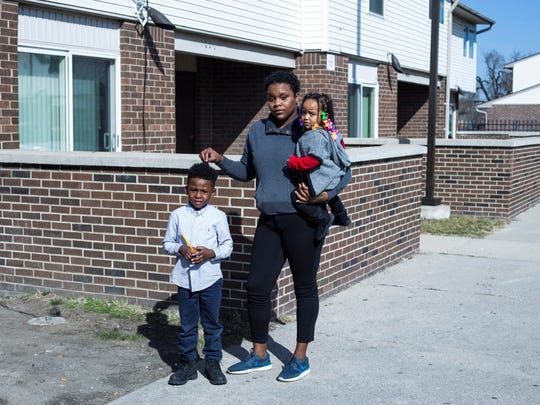 Asia Hill, holds her daughter Miasma Hill, and are with her second cousin, Deswan Blackmon, of Detroit, outside of her home in the Forest Park neighborhood in Detroit on Friday, February 23, 2017. Their apartment complex is across from the Lincoln Hall of Justice.