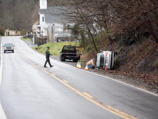 A tow truck driver and state trooper attend to an overturned