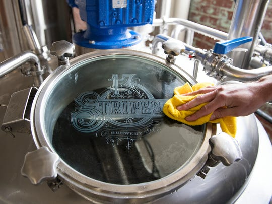 Michael Robinson, a partner of 13 Stripes Brewery, cleans off tanks at their location in Taylors Mill on Monday, March 6, 2017.