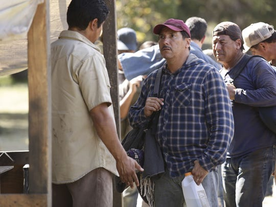 Luis Salazar (Benito Martinez), wearing a plaid shirt,