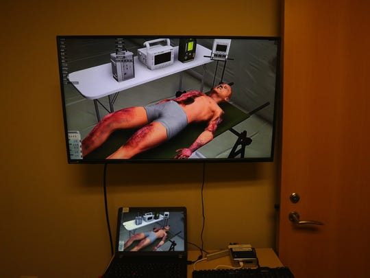 A virtual-reality display shows battlefield injuries, here on a burn victim.