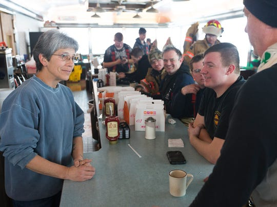 Lisle resident Laura Culver, left, chats with firefighters while they take shelter in the Skylark Diner on Tuesday morning after battling an overnight blaze at the Skylark Motel. Culver stopped into the diner early for a cup of coffee and decided to stay and help serve the firefighters.