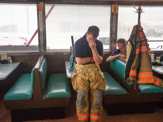 Vestal firefighter Mike Behr rests inside the Skylark Diner as emergency responders dealt with the aftermath of an overnight blaze at the Skylark Motel in Vestal on Tuesday, March 14, 2017. One person was confirmed dead and another injured.