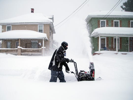 Dave Baker uses a snowblower to clean the sidewalk