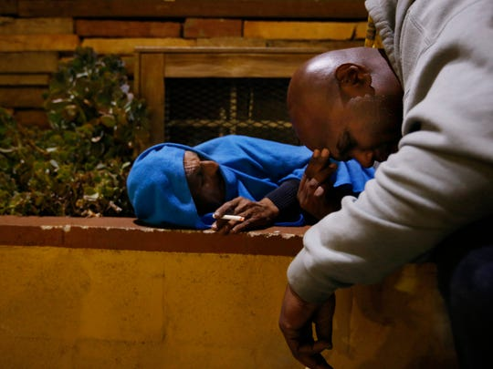 Anthony Ruffin, 48, right, kneels to speak with a homeless man sleeping in the bushes on Jan. 30, 2017 in Hollywood, Calif. (Francine Orr/Los Angeles Times/TNS)
