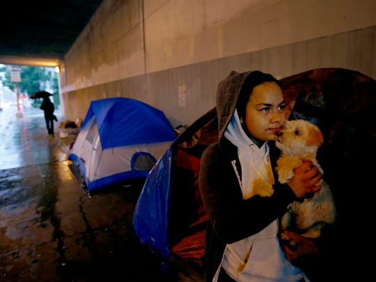 Monic Bell holds her dog Hades outside her tent in Hollywood. Bell is homeless and says she was in the foster system. (Francine Orr/Los Angeles Times/TNS)