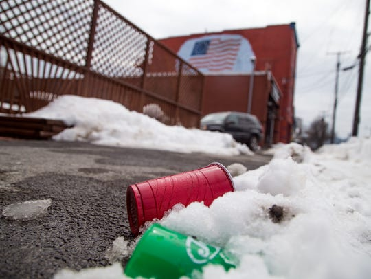 A cup lays in the snow near 92 Front St.. where a Binghamton
