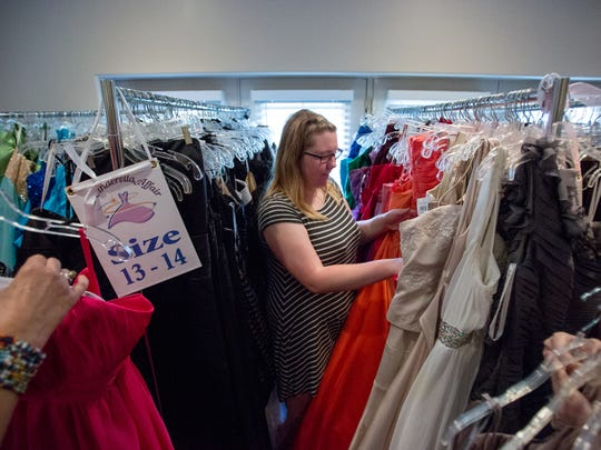 Stephanie Fall looks through the rack to pick out her prom dress at the Cinderella Affair, in Chandler, Ariz., on March 25, 2017.
