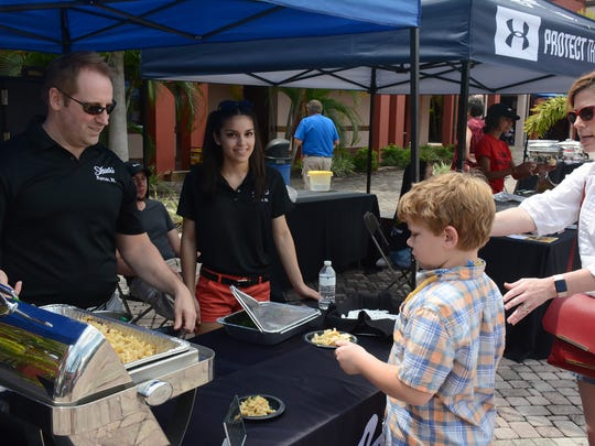 Jeff Gerome of Shula's Steakhouse hands a sample of the restaurant's crab mac 'n' cheese to Kiernan Bernaldo, 8, and gets a vote as a favorite in return.