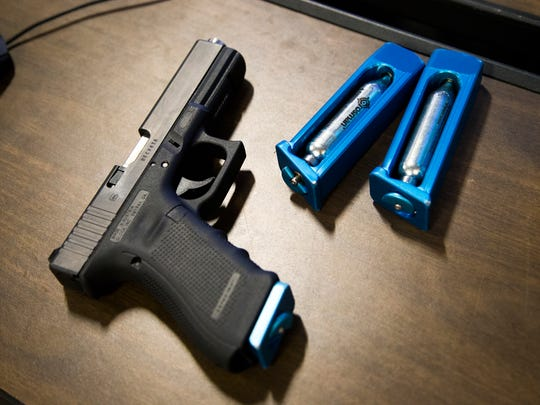 Police use real guns outfitted with CO2 cartridges to replicate recoil and lasers to mark where the officer fired during simulations.