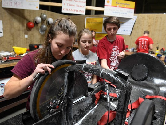 Members of the Mater Dei High School Supermileage team (L-R) Grace Cox, Taylor Lipking and Grant Weiss the wheels to the carbon fiber chassis of the team's prototype entry for the 2017 Shell Eco Marathon held in Detroit in April, March 9, 2017.