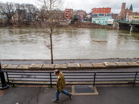 A man walks near the banks of the Chenango River in downtown Binghamton on Tuesday.