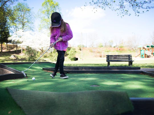 Zoey Jones, 7, of Augusta, GA uses the miniature golf course at McPhereson Park in Greenville on Friday, April 7, 2017.