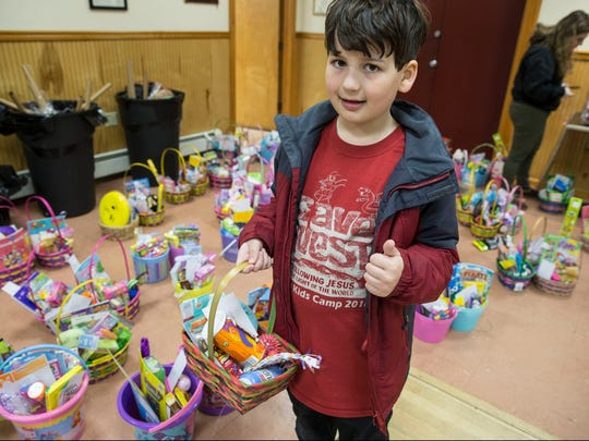 Charles Metroff, 10, of Brick helps with the baskets. Volunteers from Helping Families in Need create Easter baskets for hundreds of children in Ocean County. The organization is providing these gifts to children who may otherwise not receive one. 