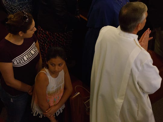 People gather for a prayer service at Our Lady of the