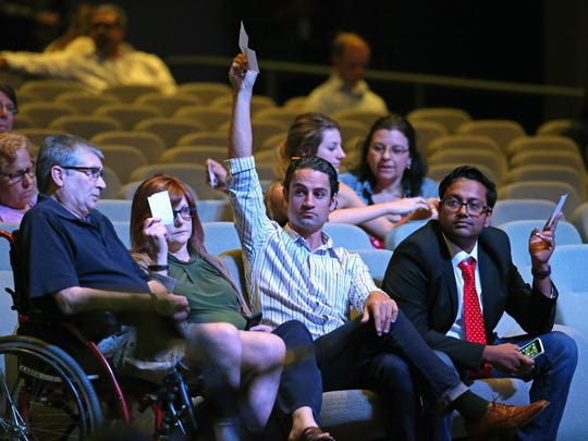 People raise their question cards  for John Giles, mayor of Mesa, and U.S. Rep. Andy Biggs as they take part in a town hall meeting at Without Walls Church on April 11, 2017, in Mesa.