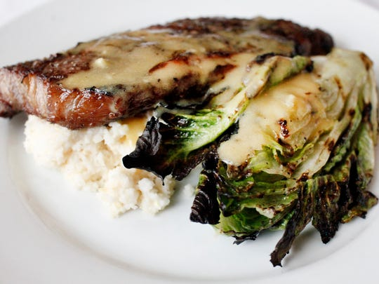 A New York Strip with a grilled romaine wedge over grits and drizzled with a red wine vinaigrette at Buck's Restaurant and Bar in Old Louisville.