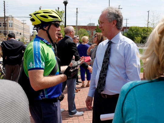 Louisville Mayor Greg Fischer, right, talks with Andy Murphy before a press conference to unveil LouVelo, the city's new bike share program. LouVelo will feature 305 bikes located at 28 stations throughout Louisville, one of which is located on the Spalding campus.  April 14, 2017