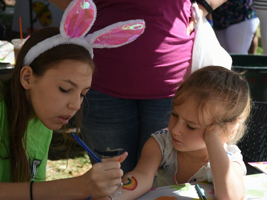 Amaia Mayberry, 5, gets her arm painted by volunteer