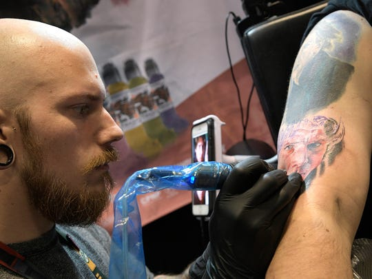 Artist Pony Lawson, left, of Chicago, works on a tattoo of Hans Solo for Jason Stone, of Tampa, Fla., during the Star Wars Celebration event Friday, April 14, 2017 in Orlando, Fla.