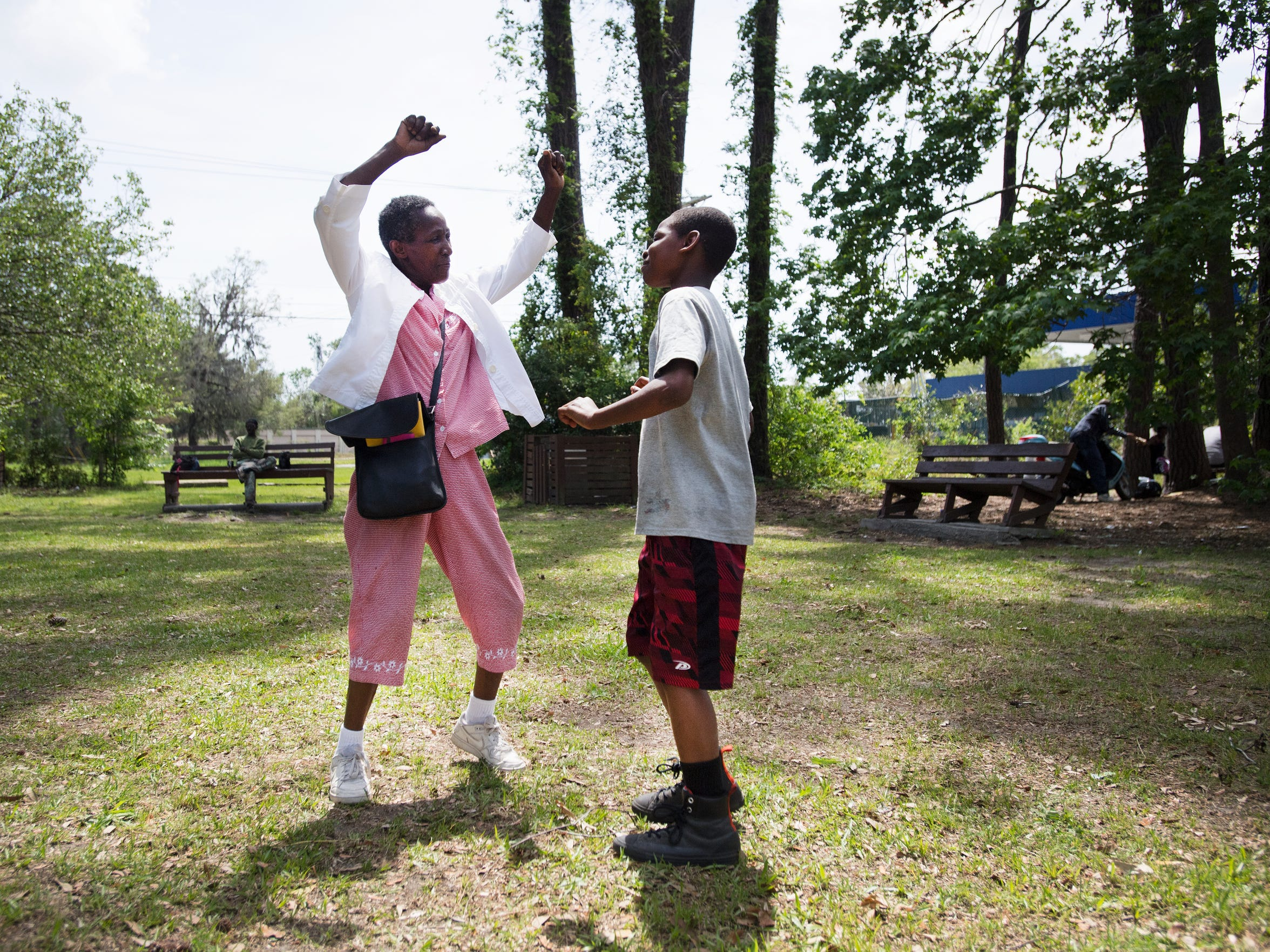 Peatsy Smalls, 63, teaches Jeden Pope, 10, how to dance at an outdoor market on St. Helena Island on Saturday, April 15, 2017.
