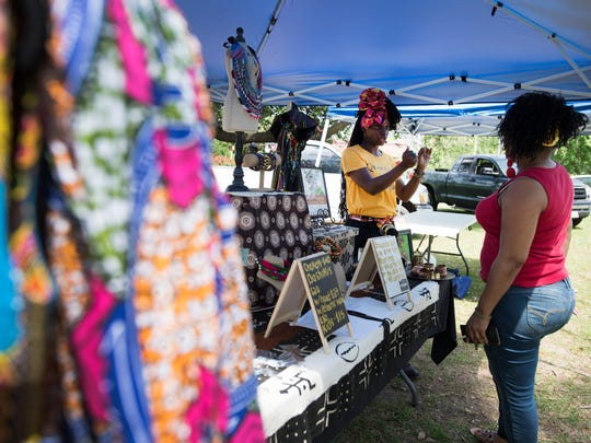 Two Gullah-Geechee women speak at a table selling clothing and accessories at an outdoor market on St. Helena Island on Saturday, April 15, 2017.
