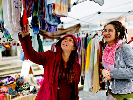 Sarah Guyer, left, of York City, looks at onesies dyed by Tiffnay Morgan, of Love Peace and Dye, during Go Green Day in York City, Saturday, April 22, 2017. Dawn J. Sagert photo