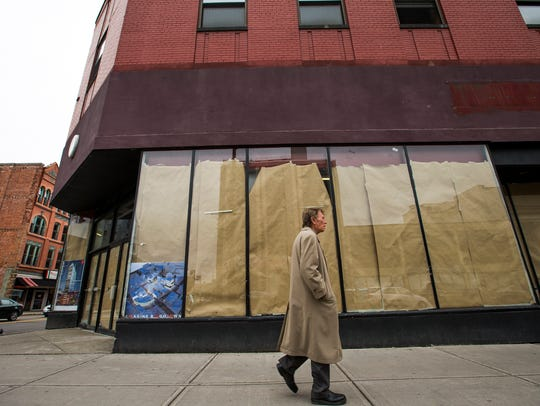 A man walks in front of 60 Court St. in downtown Binghamton