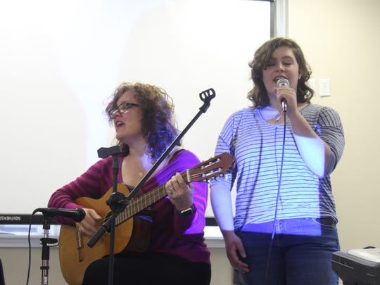 Isabella Parker, 17, right, sings with her mother Natasha Helfer Parker during a gathering of Wichita Oasis.