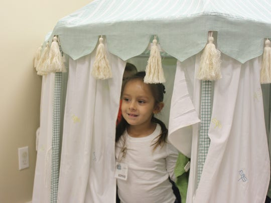 Sophie Pena, 4, peeks out of a tent in the children's area of Wichita Oasis before the program begins on a Sunday morning.