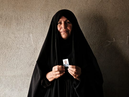 Ghanya Juma Sultan, 51, holds a picture of her deceased