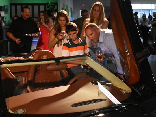 Mark Messina looks over the car with family members Mya, Marcus and Michelle. Naples Motorsports held an unveiling for the new Spyker C8 Preliator Spyder, a limited-production, high-performance two-seater from a Dutch manufacturer, on Friday, May 5, 2017, at the Naples Motorsports showroom on Airport-Pulling Road.
