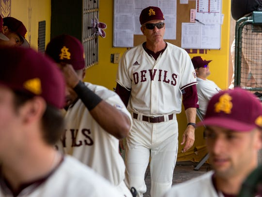 Coach Tracy Smith walks through the dugout during the