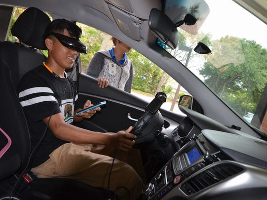 "Wearing virtual reality glasses, a student follows instructions to use his phone while ""driving"" the stationary vehicle. Naples High School students experienced a simulation to demonstrate the danger of texting while driving on Friday, May 5, in a program sponsored by State Farm Insurance."