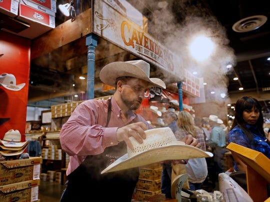 Bryan Scott adjusts the shape of a cowboy hat at the Houston Livestock Show and Rodeo.